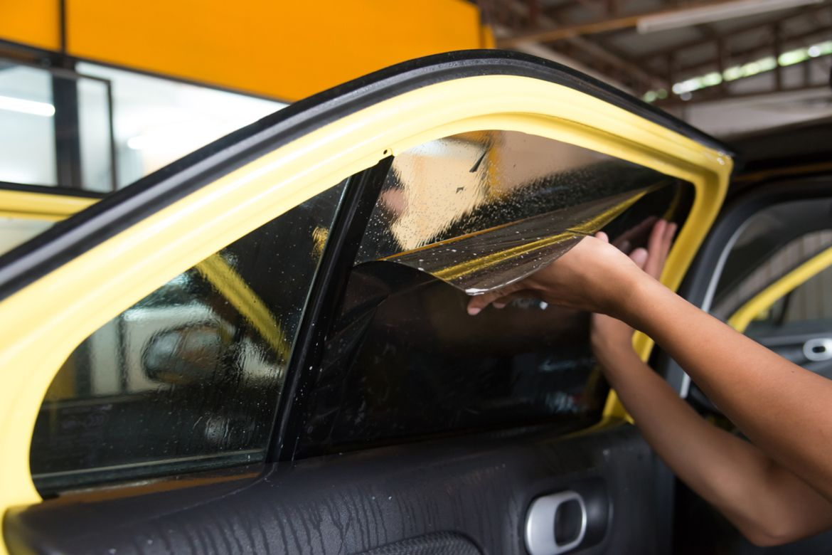 car window tint being removed by mechanic