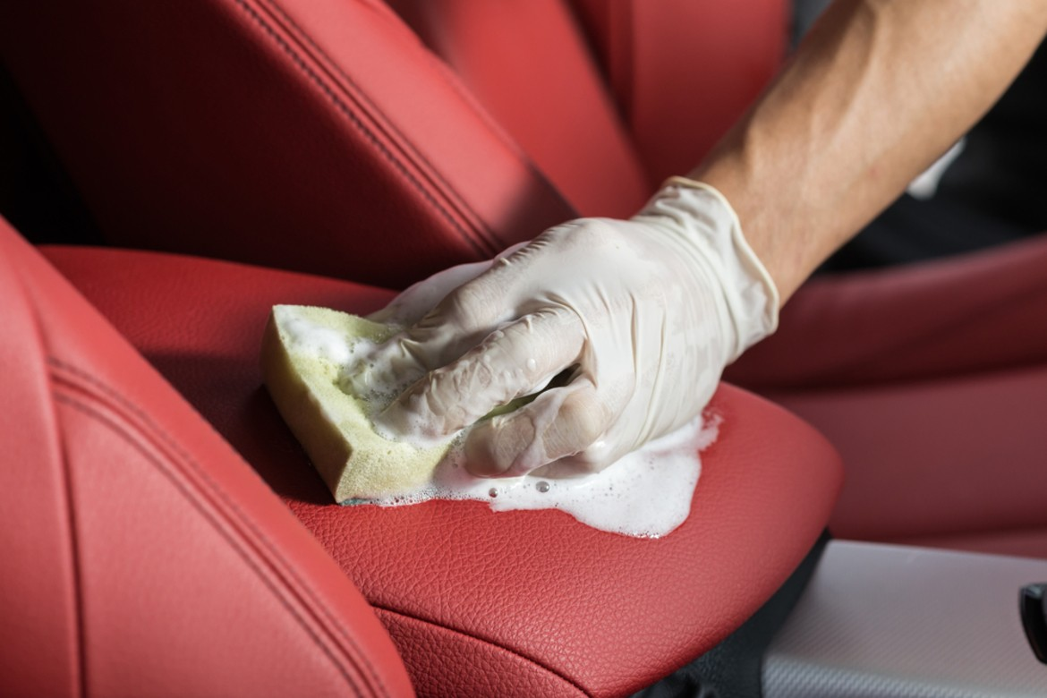 man carefully scrubbing his red leather car seat