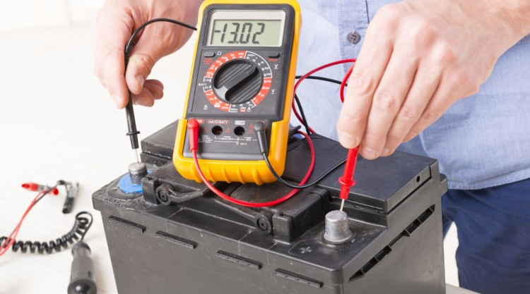 A car battery being tested with a multimeter
