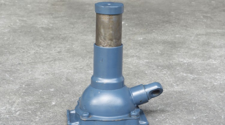 A blue hydraulic bottle jack on a concrete floor