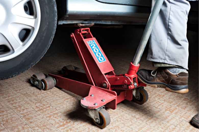 A red floor jack lifting a silver car during a tire change