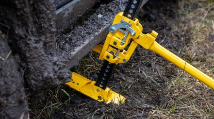 A yellow high lift jack being used to lift a 4x4 that's stuck in some deep mud