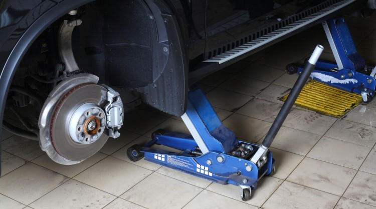A blue floor jack under a car having it