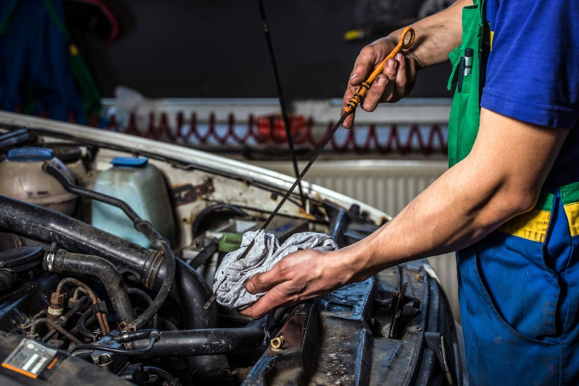 Mechanic with tools, a towel and dirty hands while performing an oil change on a car