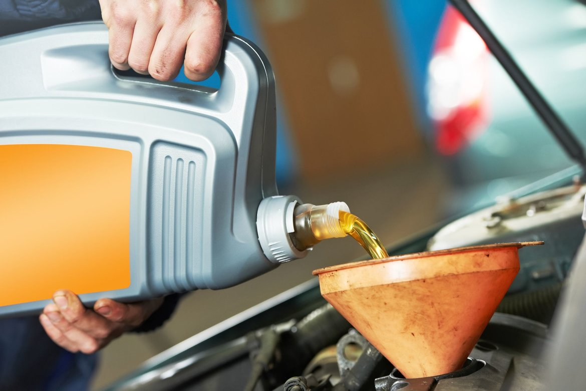 pouring oil into a car after figuring out how much it needs