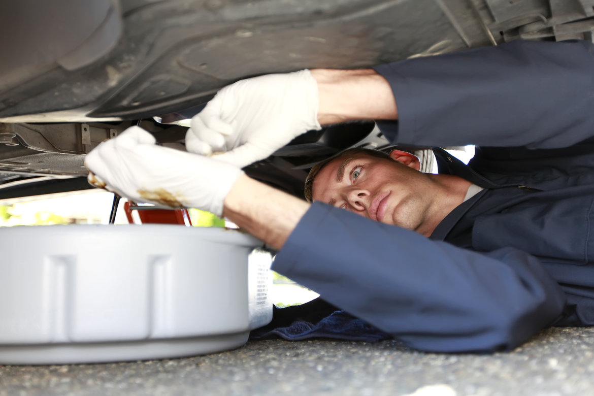 Mechanic performing car oil maintenance tasks underneath a vehicle