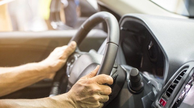 Man with two hands on the steering wheel trying to impose full control