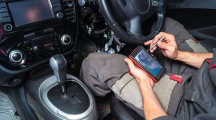 Man sitting in car, readinf from a smartphone the info sent by a Bluetooth obd II scanner