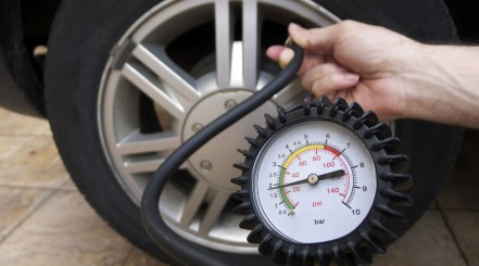 Close up of a pressure gauge in front of a car wheel, from a portable air pump for car tires
