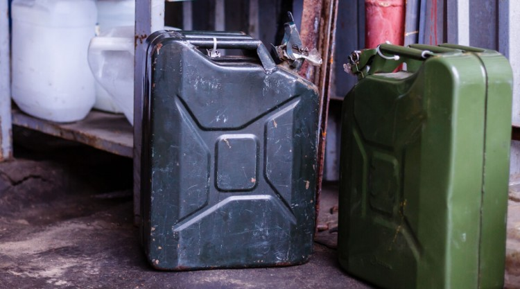 2 old fashioned military style jerry cans on a garage floor