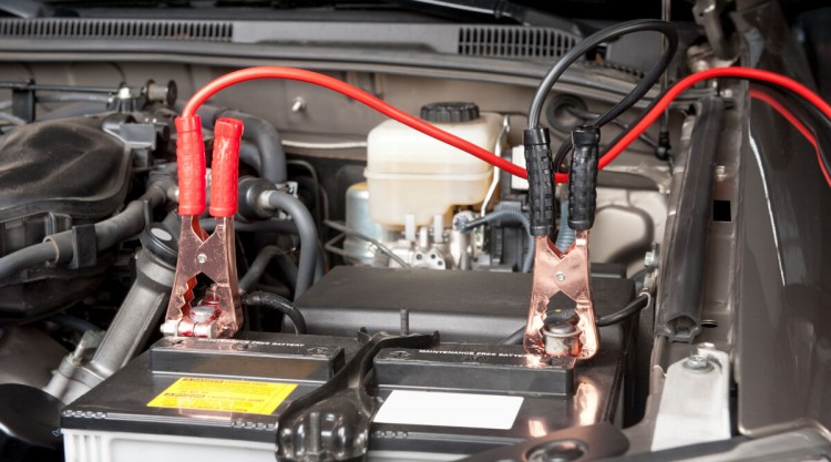 Battery maintainer cables transferring power to a battery still in the engine compartment