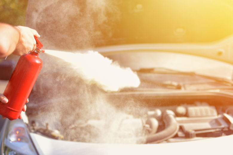 A man holding a red fire extinguisher, spraying it into the engine bay of a car