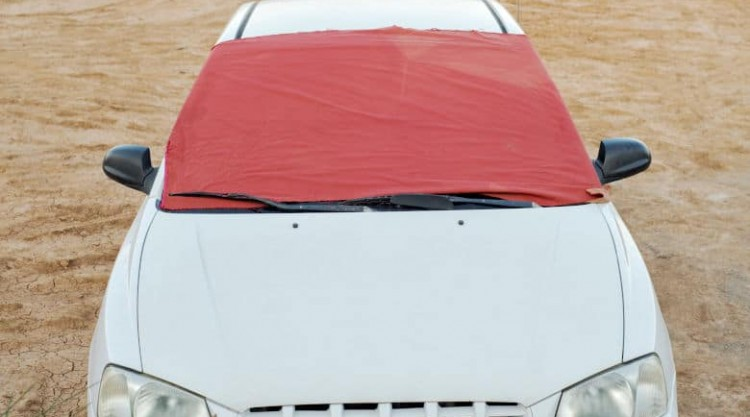 A white car with a red windshield cover