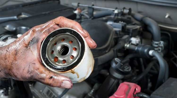 A mechanic holding an oil filter, with a car engine in the background