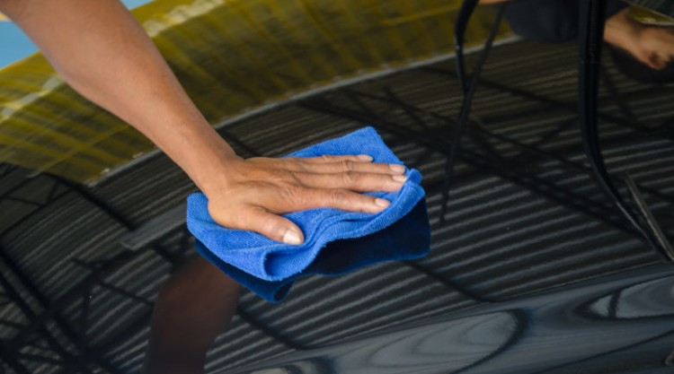 Man waxing bonnet of a black car with a blue cloth