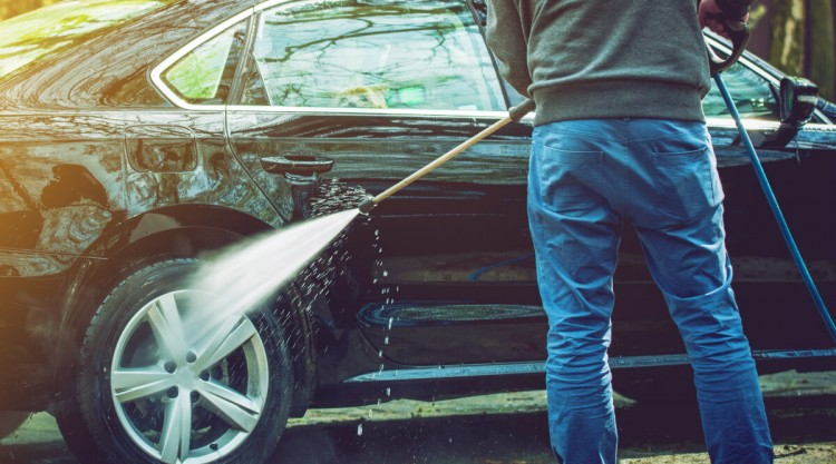Man with pressure washer cleaning the rear wheel of his black car