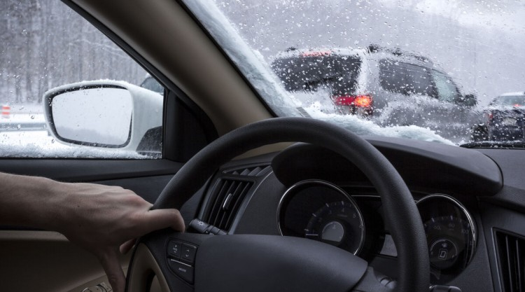 Photo through inside of a car windscreen, driving on a cold, snowy day