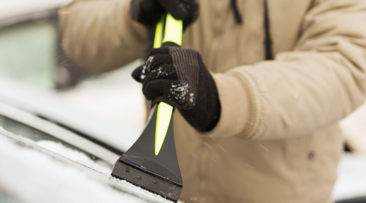 A man using an ice scraper on a car windscreen