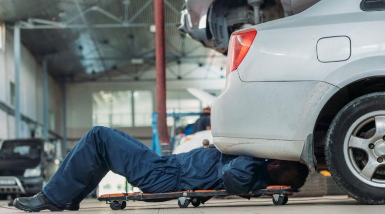 A mechanic sliding on a creeper under a silver car