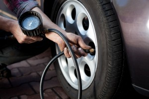 A mechanic using a tire pressure gauge outside on a front tire
