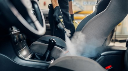 A mans hand using a steam cleaner to clean car upholstery