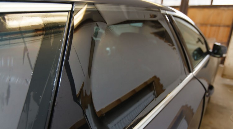 Side view of a black car with dark window tint