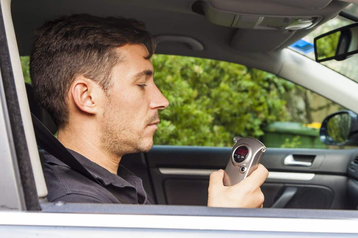 Man in his parked car operating a breathalyzer in his hand