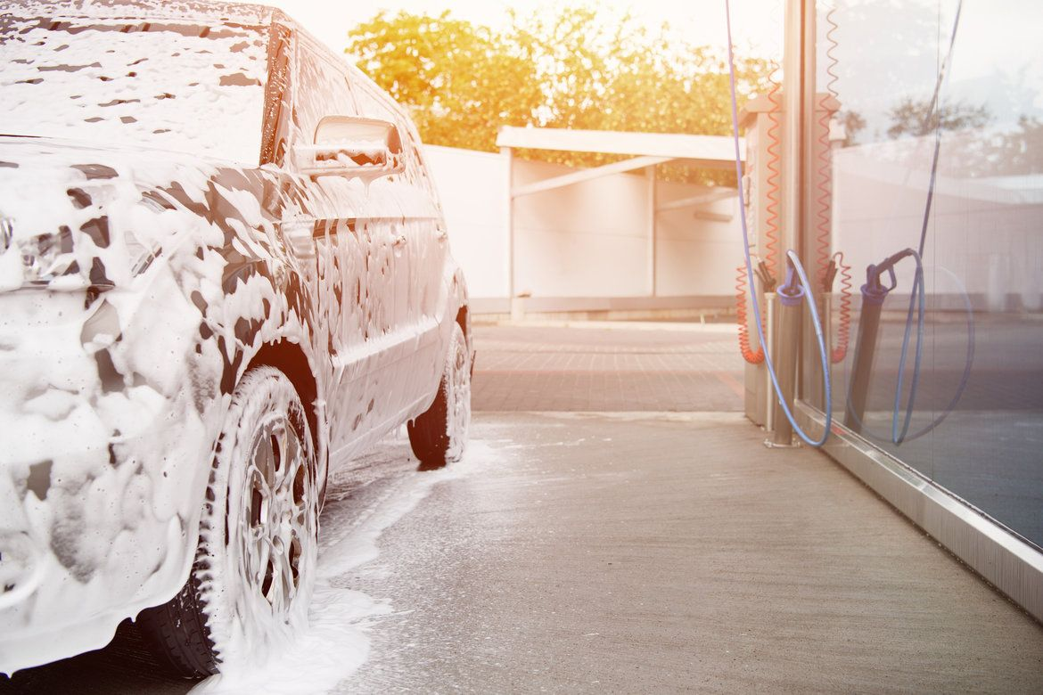 A car with foam all over its exterior, and a foam cannon next to it