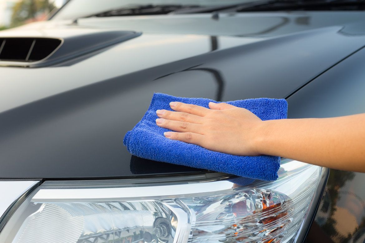 Woman cleaning the hood of her car with a microfiber towel