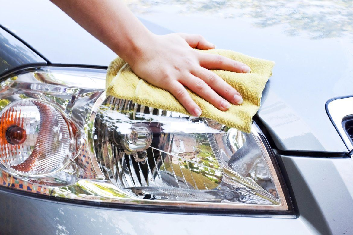 Man wiping car headlights and hood clean with a towel