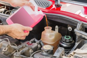 Man pouring pink antifreeze from bottle into the car