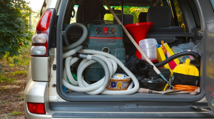 The trunk of an SUV fully and messily loaded with cleaning supplies