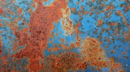 Close up of rust on a panel of a blue car