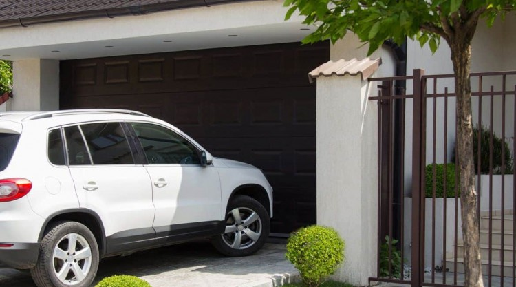 A white SUV approaching the garage parking door