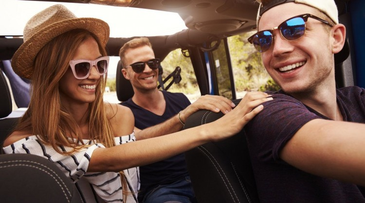 Two guys and a girl in a car, wearing sunglasses for protection from the sun while on the road