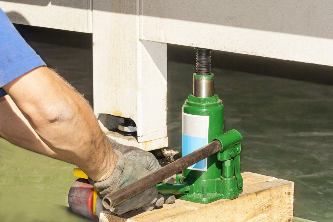 A Mans gloved hand operating a green bottle jack