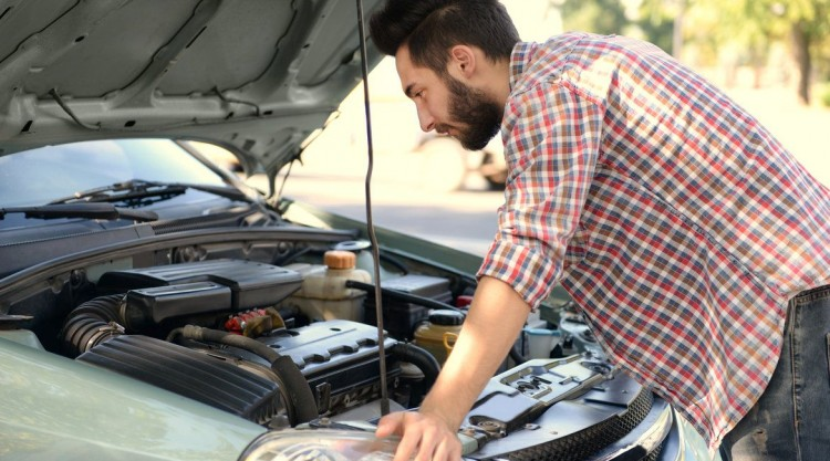 Young man inspecting the hood of his vehicle on the side of the road because of overheating problems