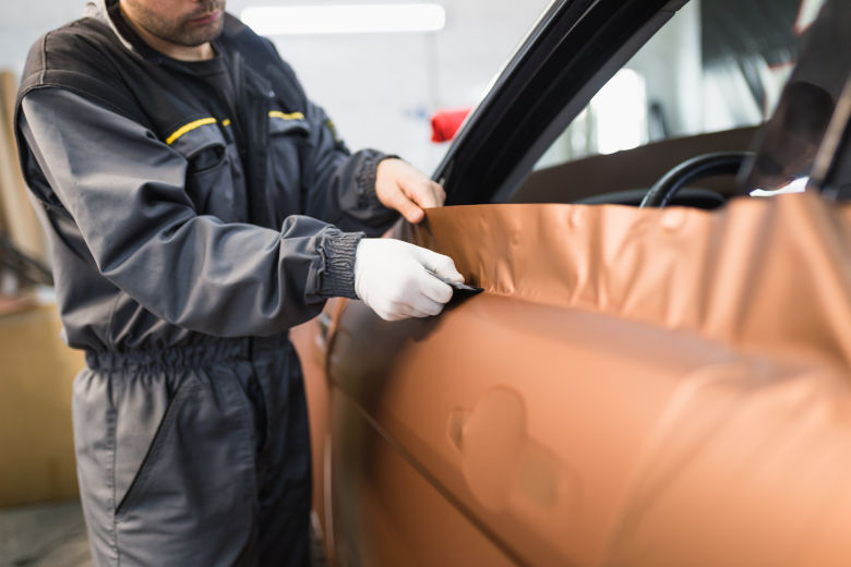 Man applying a bronze colored wrap to the exterior of a car