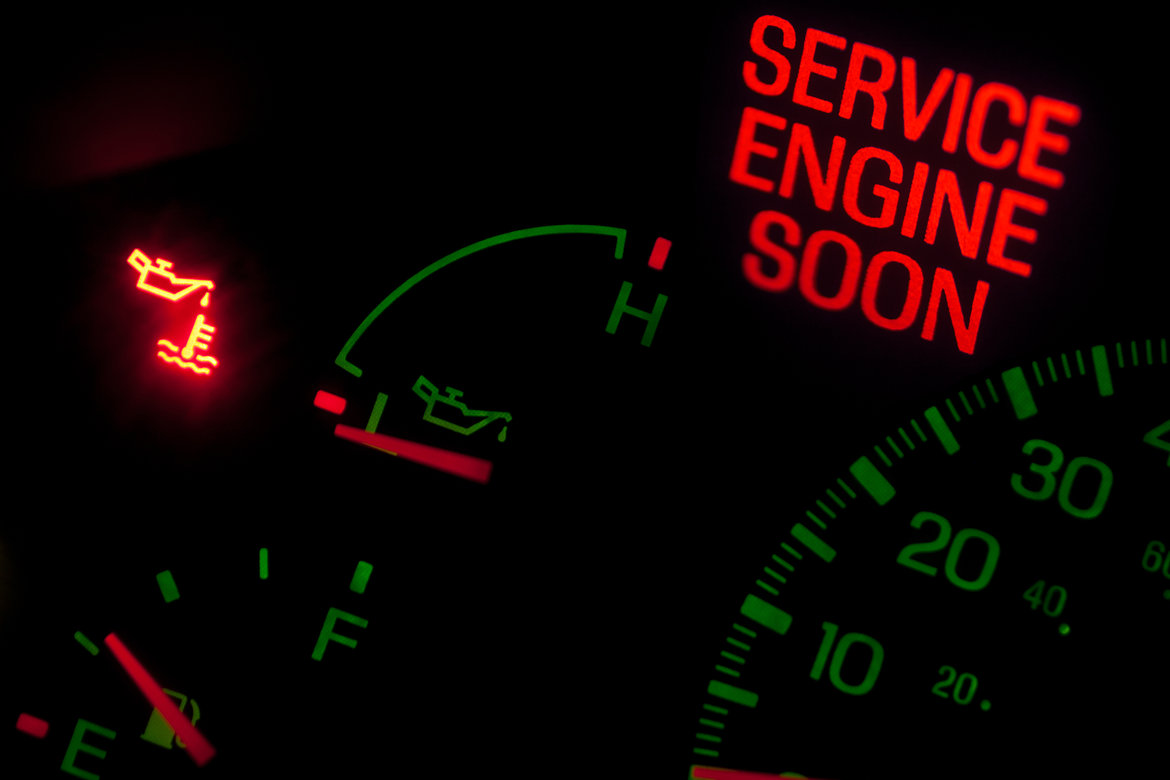 Car dashboard lights illuminating to warn of possible engine problems