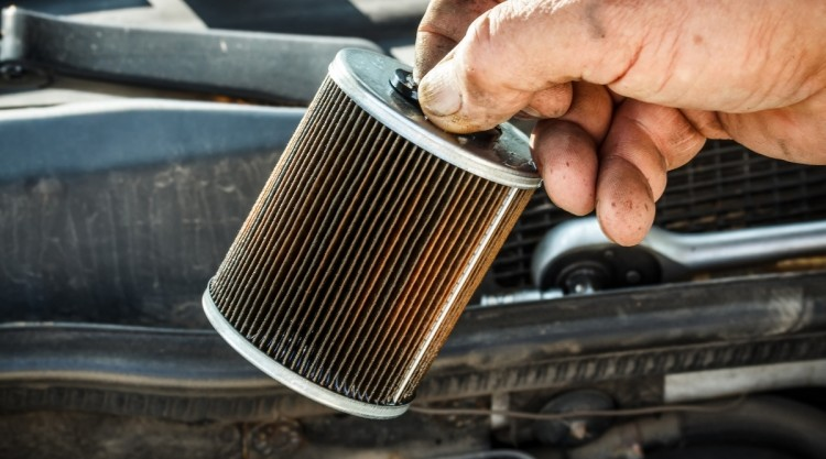 Mechanic holding a dirty fuel filter that needs replacement