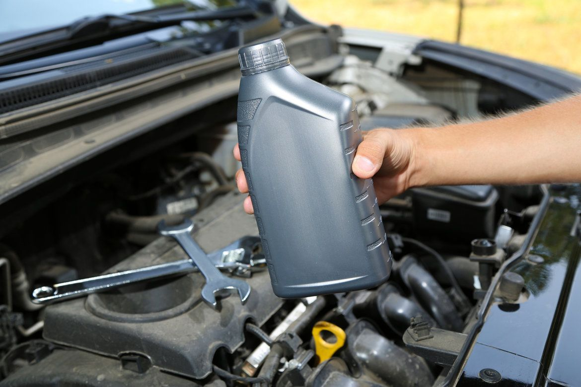 Car hood open with tools inside and a man holding a bottle of motor oil