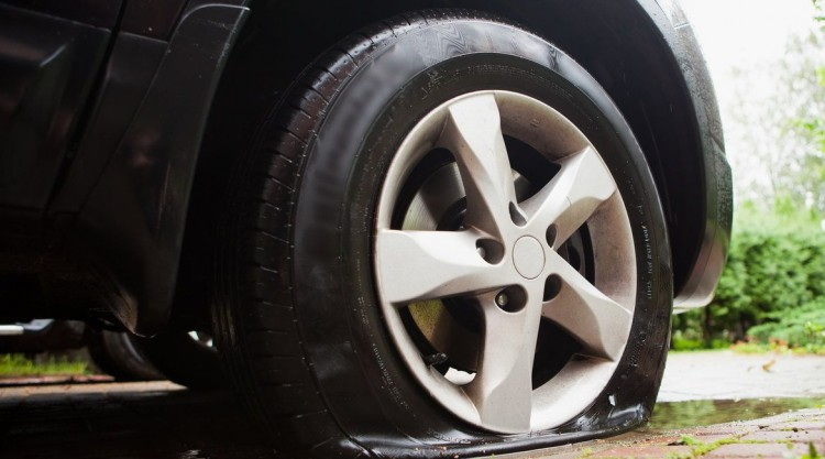 Black car parked at home with a flat tire that