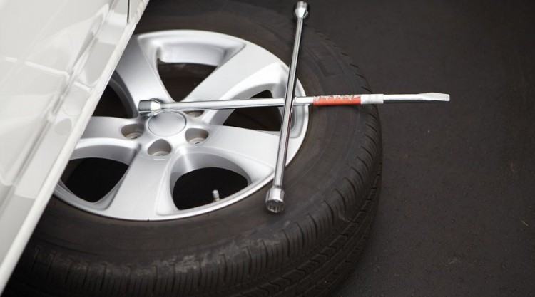 Spare tire being installed on a car to drive on