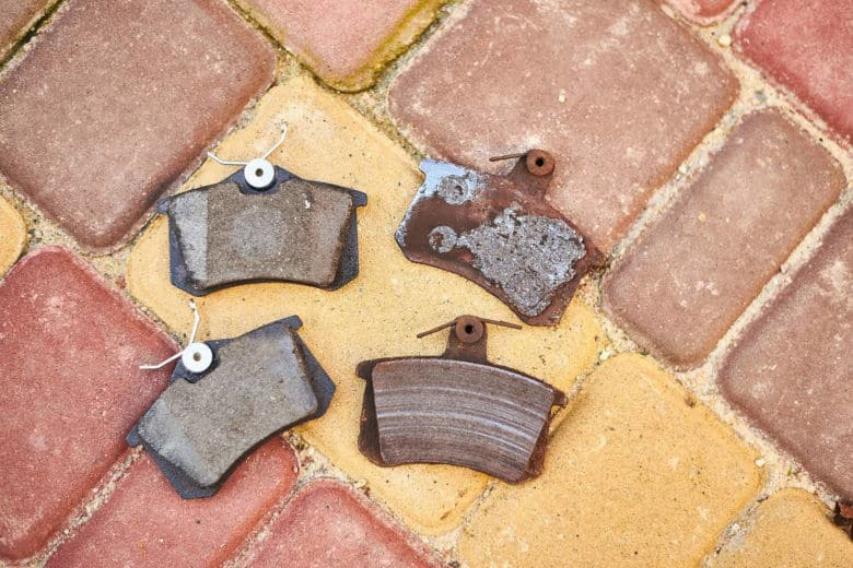 4 used and worn out brake pads laid on brick ground floor