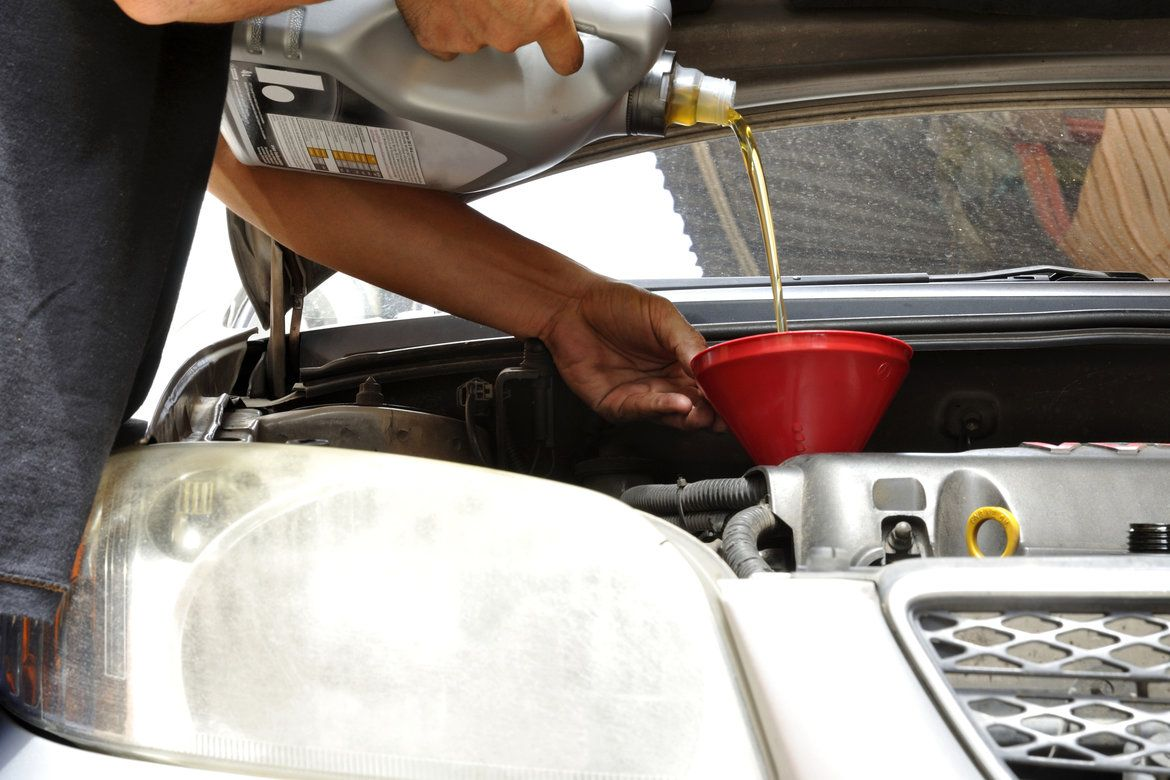 Car owner with vehicle's hood open and performing a routine oil change task