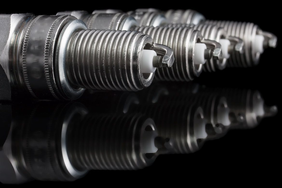 4 brand new spark plugs on a black background