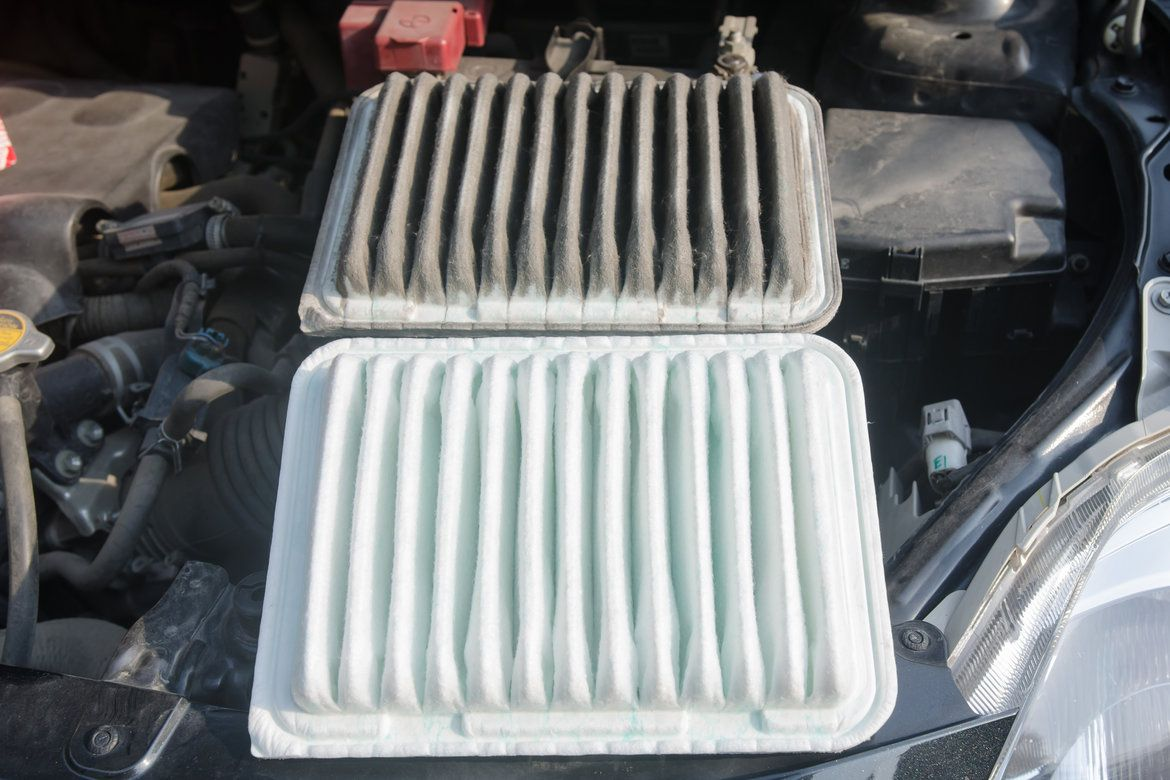 Picture of a dirty, black looking cabin air filter placed next to a clean, white looking one