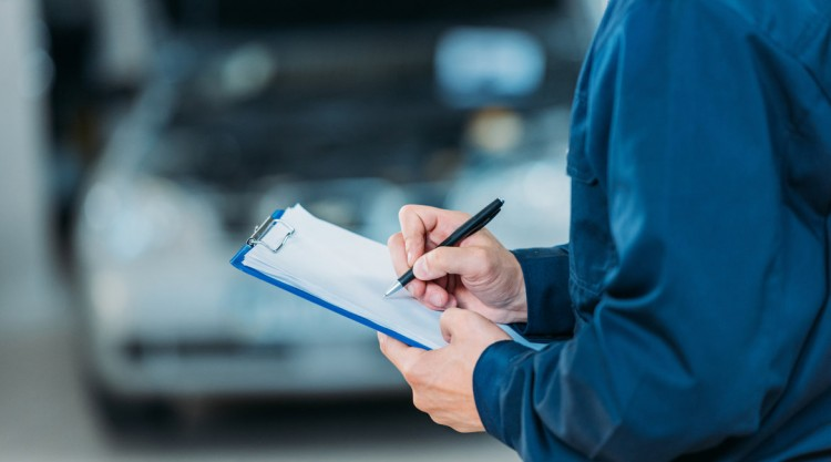 Mechanic holding a notebook and pen to jot down notes about a car