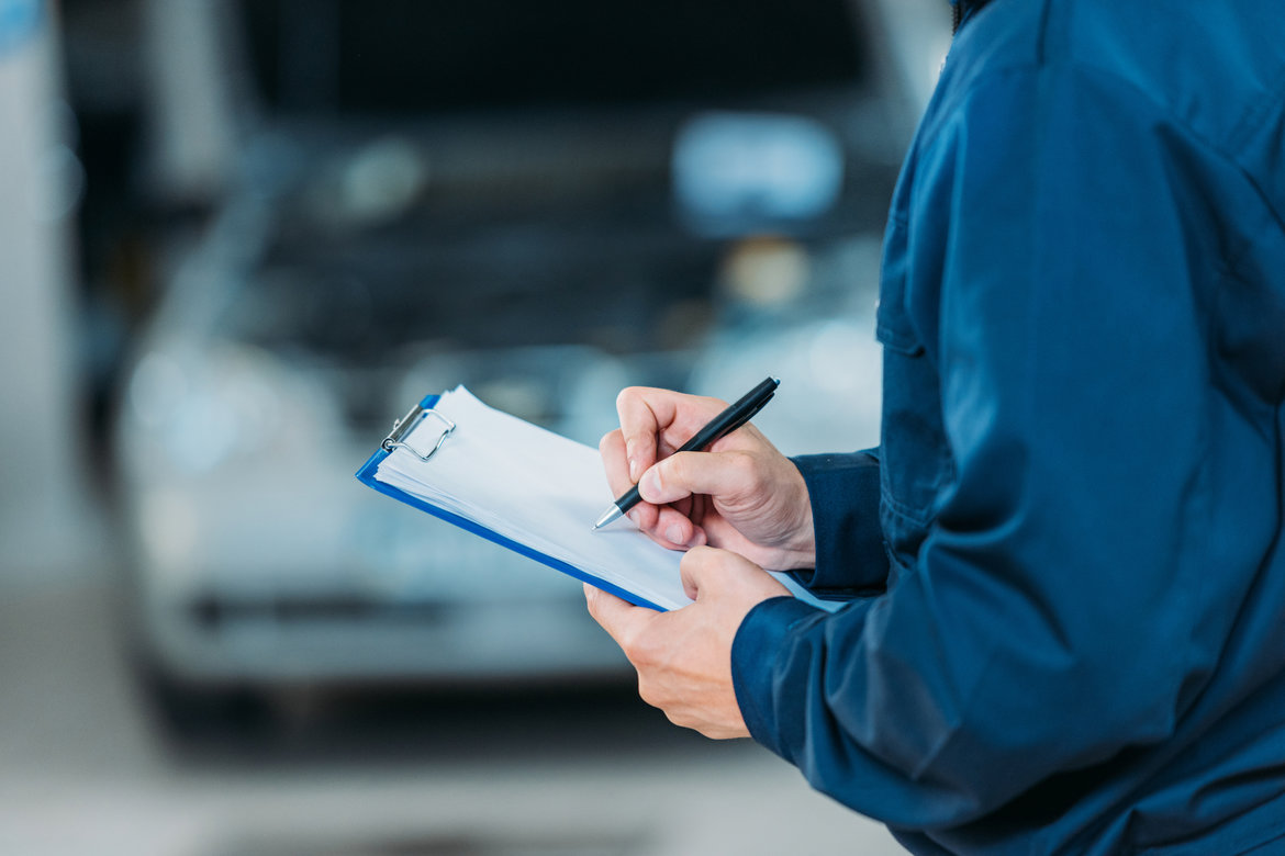 Mechanic holding a notebook and pen to jot down notes about a car's maintenance tasks