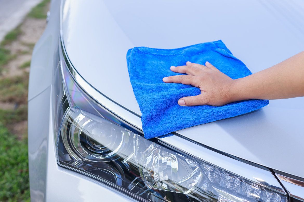 Man wiping silver car hood clean with a towel after removing tar from it